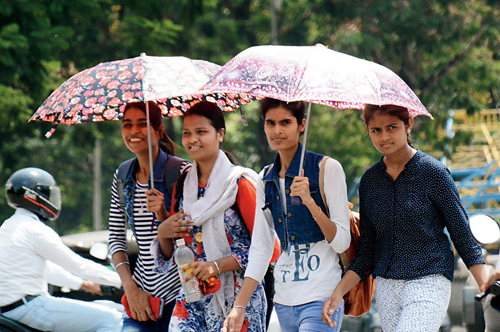 Students use umbrellas on a hot Monday afternoon at Sakchi, Jamshedpur.