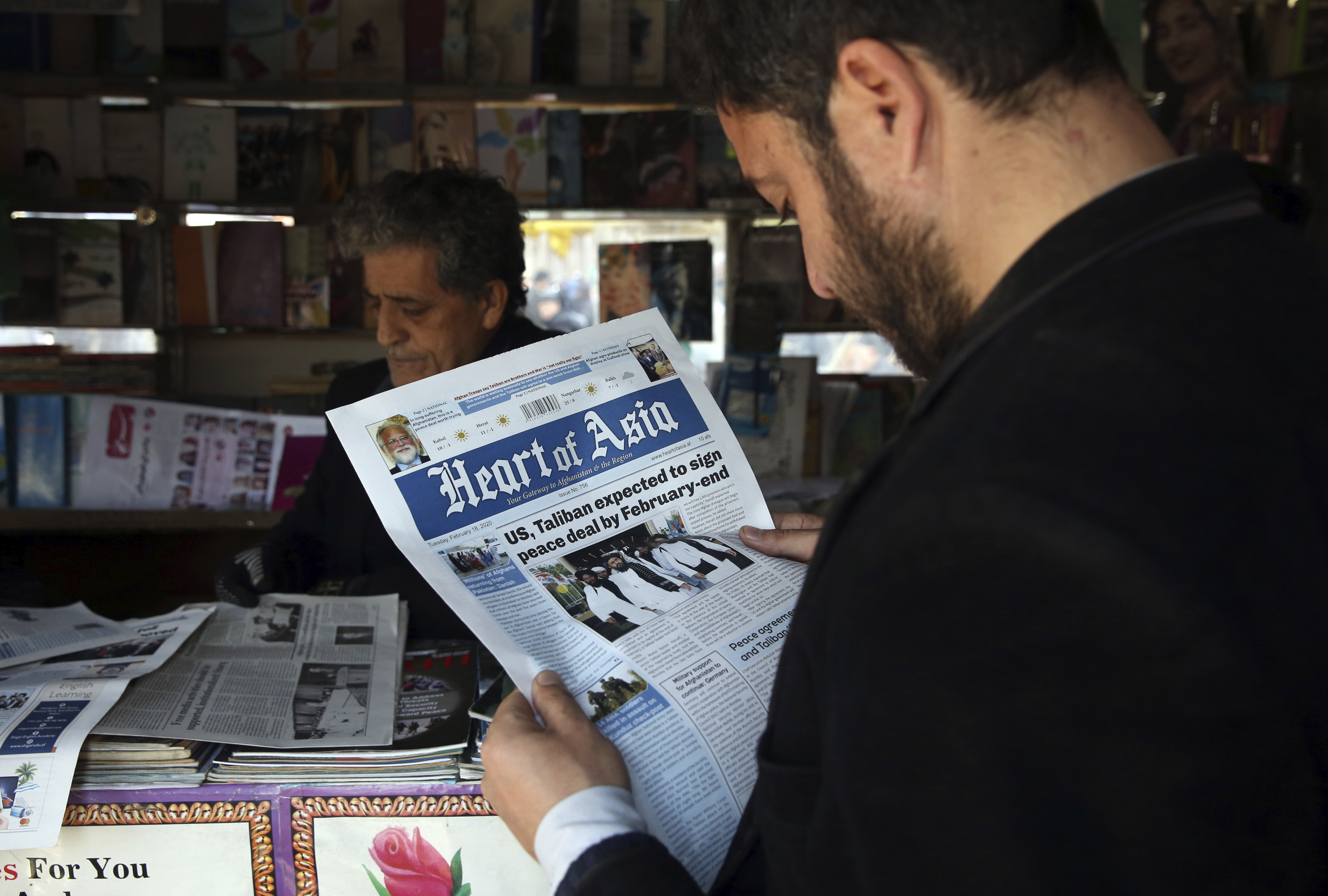 A man reads a local newspaper about peace talks in Kabul, Afghanistan
