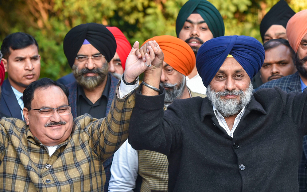 J.P. Nadda (L) and Sukhbir Singh Badal join hands during a joint press conference regarding their parties alliance for the Delhi Assembly elections