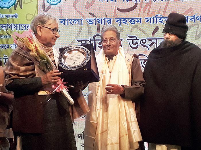 Ganesh Haloi receives the award from Debesh Roy as Joy Goswami looks on at Rabindra Okakura Bhavan