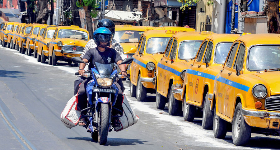 A biker rides past taxies parked along a road during the nationwide lockdown in wake of deadly coronavirus outbreak, in Calcutta on Monday