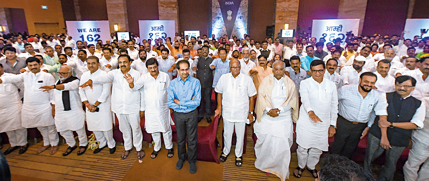 Uddhav Thackeray (in blue shirt) and Sharad Pawar with the MLAs of the Shiv Sena, NCP and the Congress at the Grand Hyatt hotel in Mumbai on Monday.