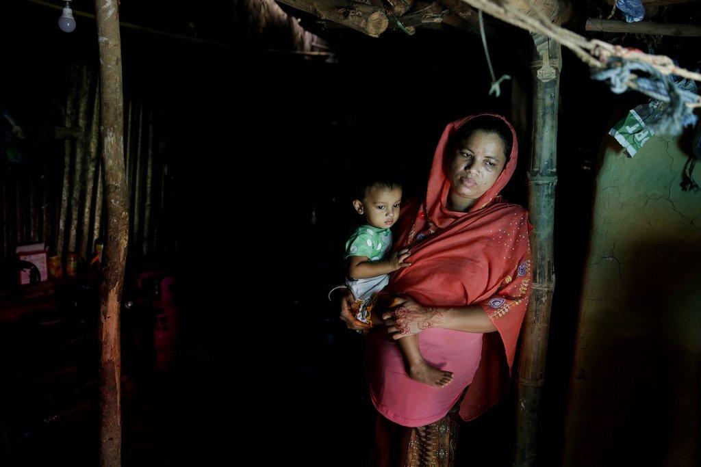 Minara Begum, mother of Rahima Akter, holds her youngest daughter Arohi Zannat.