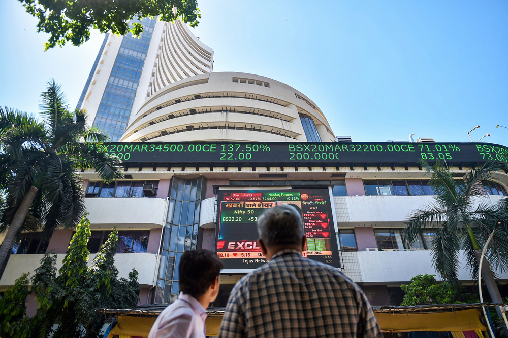 People watch the Sensex on a screen outside Bombay Stock Exchange (BSE) in Mumbai, Thursday, March 19, 2020. Equity benchmark Sensex ended 581 points lower in a highly volatile session on Thursday amid heightened fears of a global recession triggered by the coronavirus pandemic.