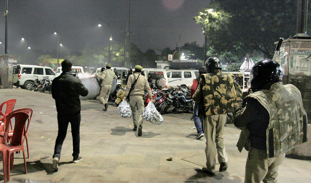 Policemen, who held a march around the Ghanta Ghar in Lucknow on Saturday evening, walk away with blankets, mattresses and other material that volunteers had brought for the women and children protesters