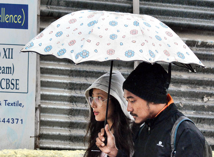 Youths use umbrellas to protect themselves from the rain in Guwahati on Friday.