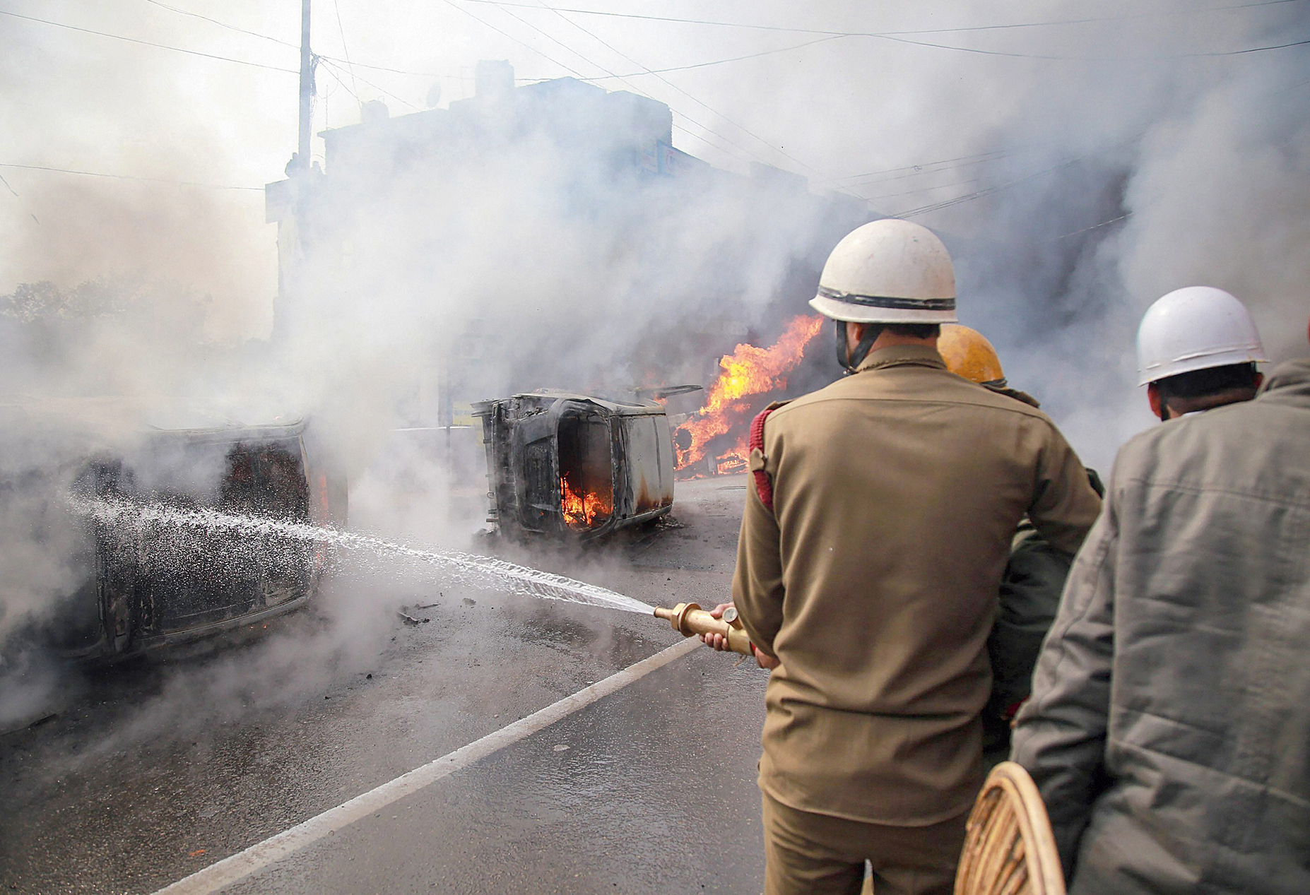 Firemen spray water to douse the flames on the vehicles that were set ablaze during a protest in Jammu on Friday.