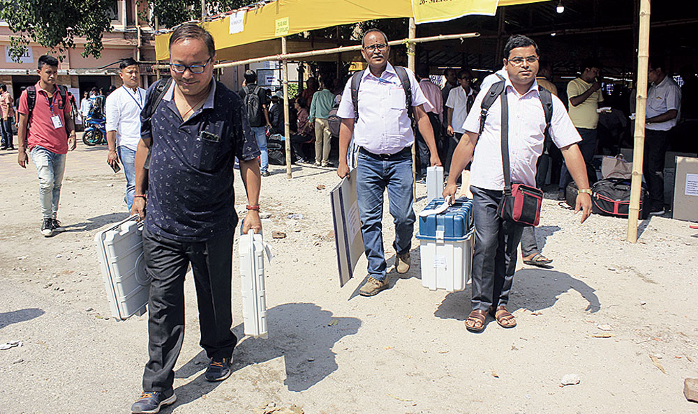 Polling personnel leave a distribution-cum-collection centre in Siliguri on Wednesday