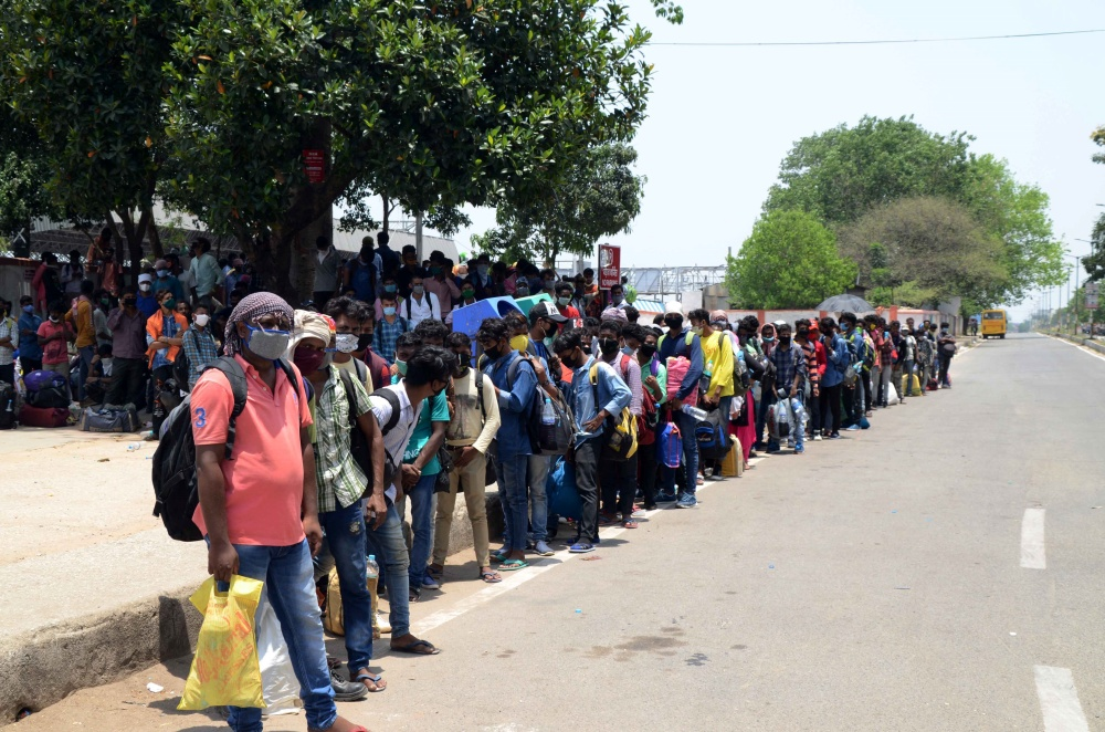 Migrant labours waiting for a bus at Hatia railway station in Ranchi