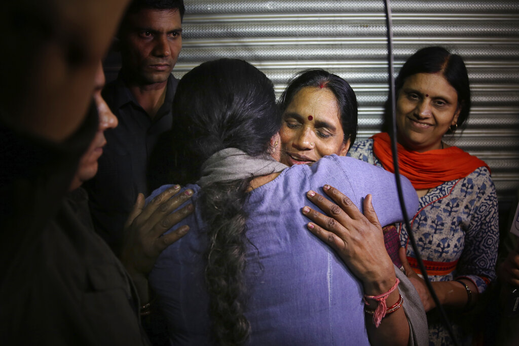 Asha Devi, mother of the victim of the fatal 2012 gang rape on a moving bus, facing camera, is embraced by an unidentified woman after the rapists of her daughter were hanged, in New Delhi, India, Friday, March 20, 2020. Four men were sentenced to capital punishment for the 2012 gang-rape of a 23-year-old physiotherapy student on a moving bus in New Delhi have been executed.