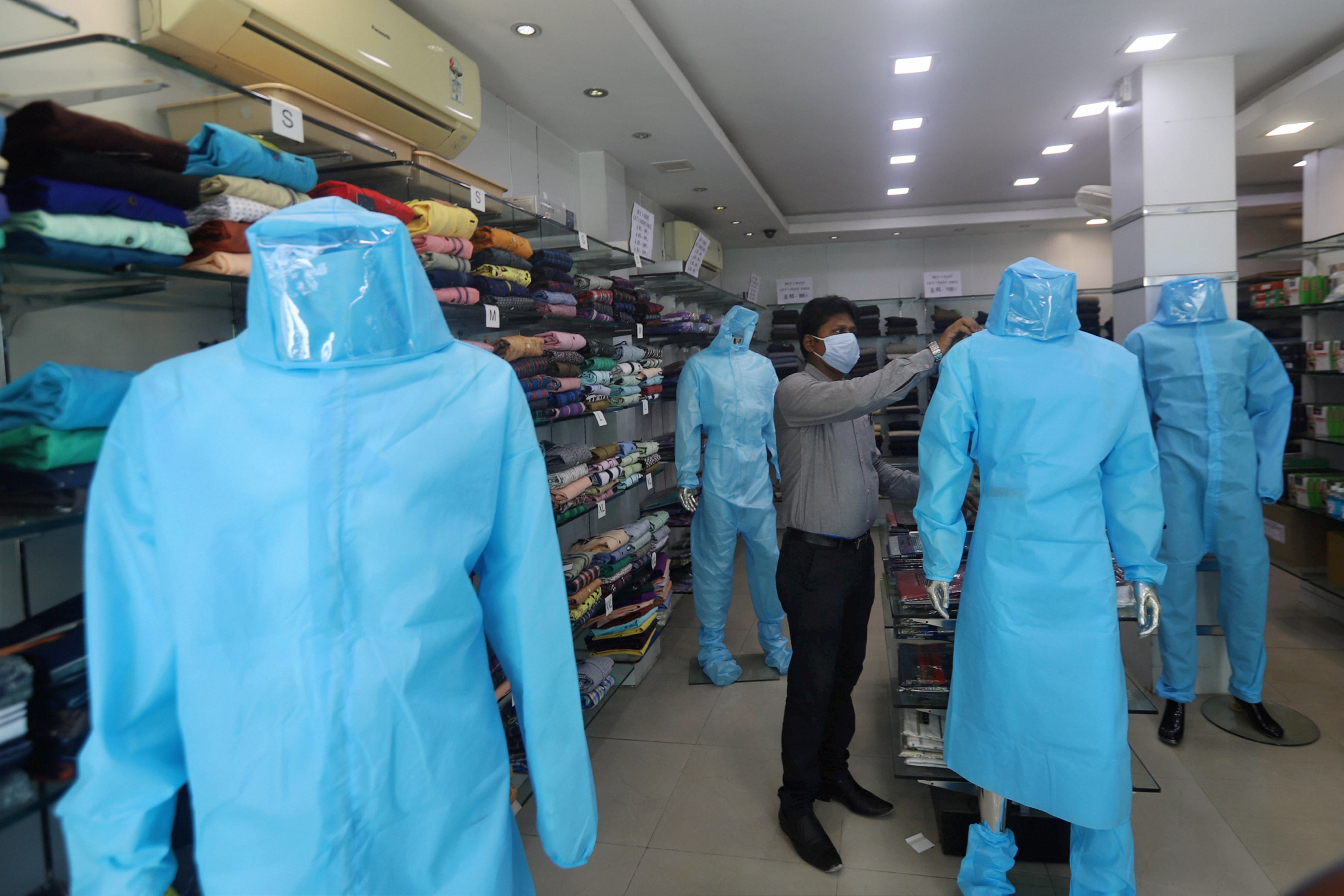 A shopkeeper puts a protective suit on a mannequin for sale at a garment shop after the government eased restrictions during the nationwide lockdown, in Chennai Thursday, May 28, 2020.
