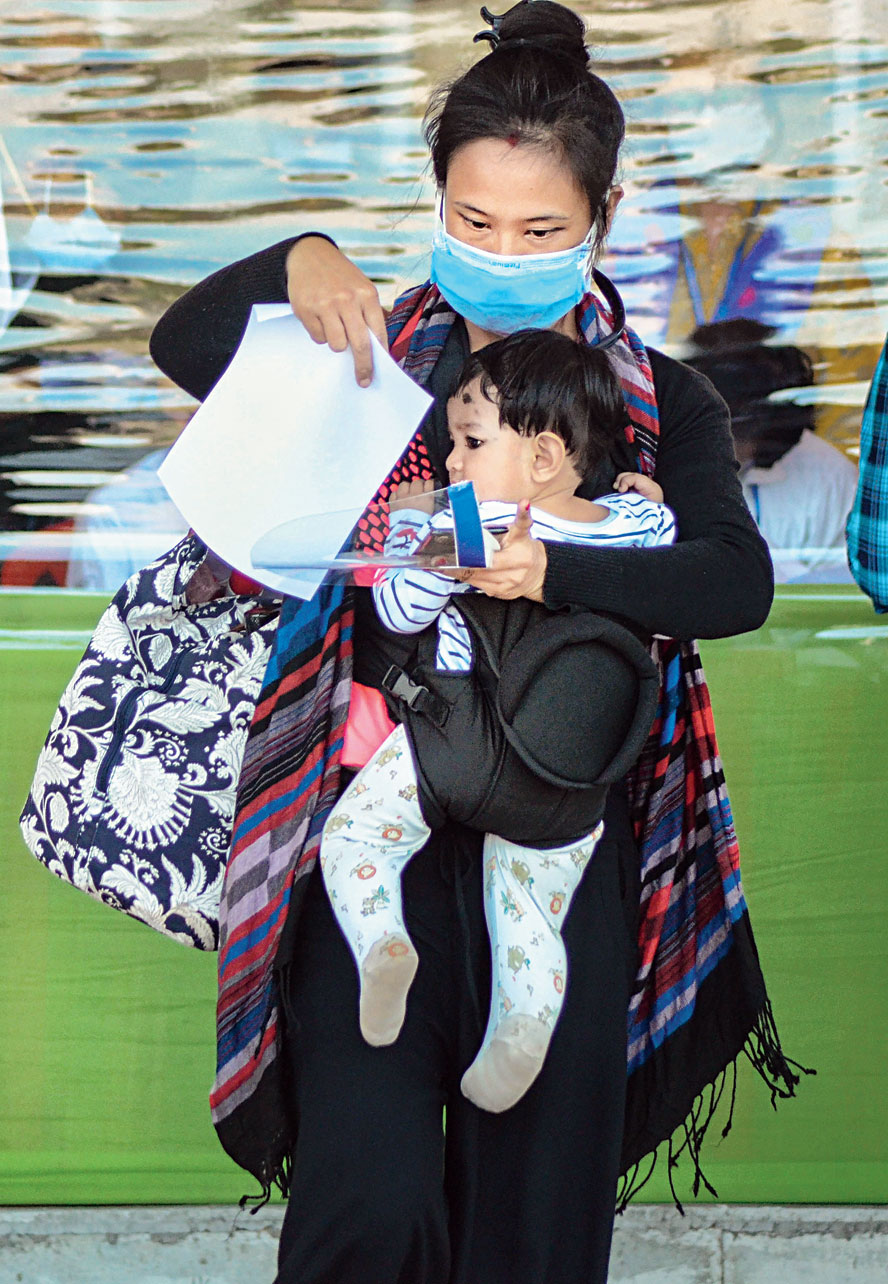 A passenger balances her child and documents after arriving at Mohanbari airport in Dibrugarh on Thursday from Calcutta.