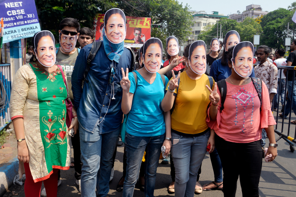 Students in masks of the West Bengal chief minister Mamata Banerjee at an election rally in Calcutta in April 2019. Banerjee's government must govern responsibly, handle law and order firmly, and crack down on corruption and nepotism.