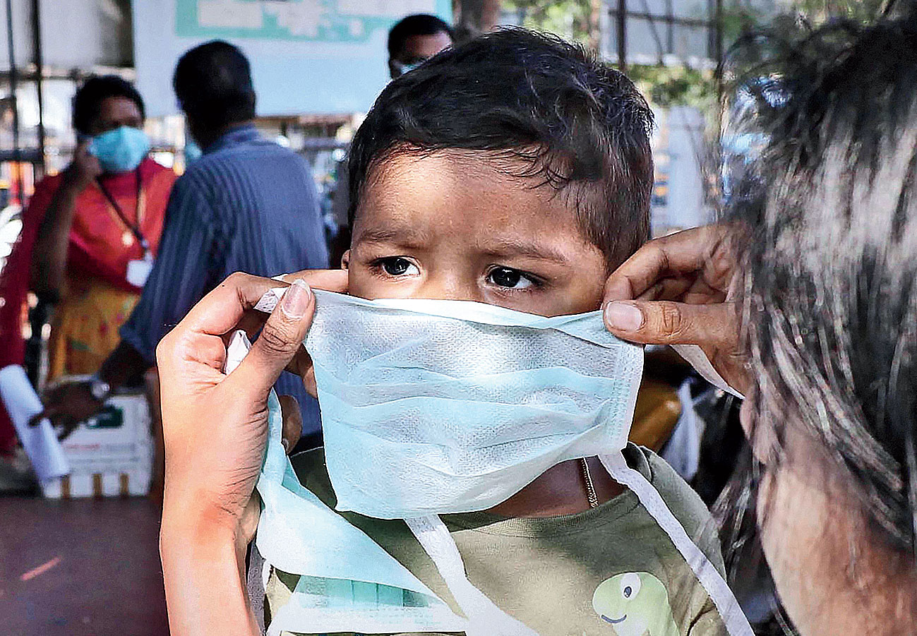 A parent places a medical mask on a child as a precaution at a hospital in Thrissur, Kerala, on Friday.