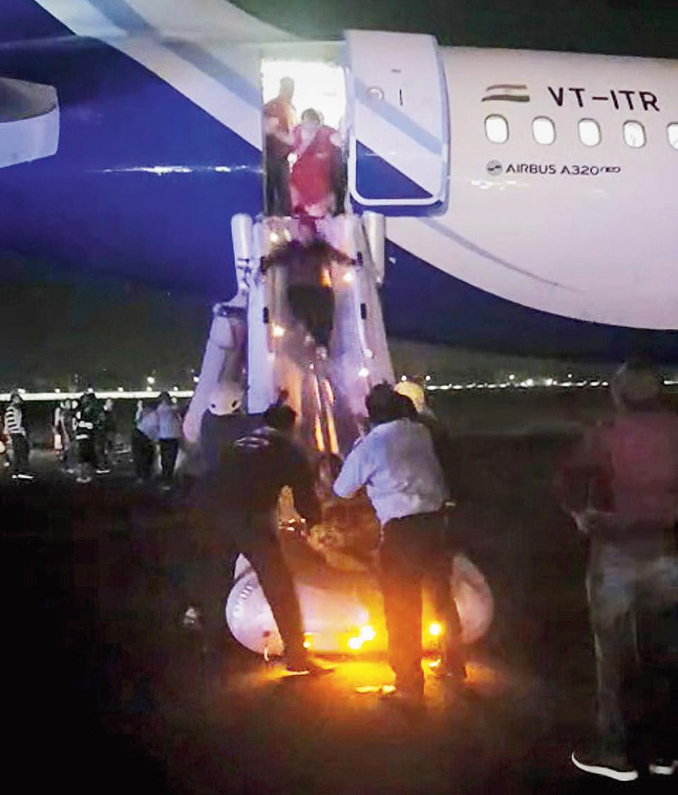 Passengers slide down an evacuation chute of the IndiGo aircraft.