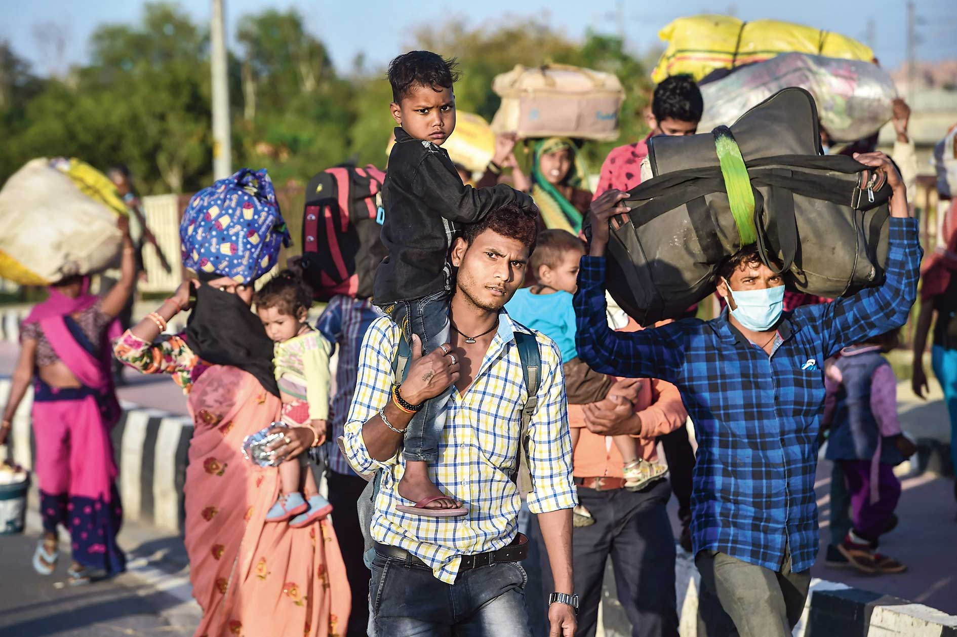 Migrant workers along with their family members walk to their native village during the lockdown in New Delhi on Sunday.