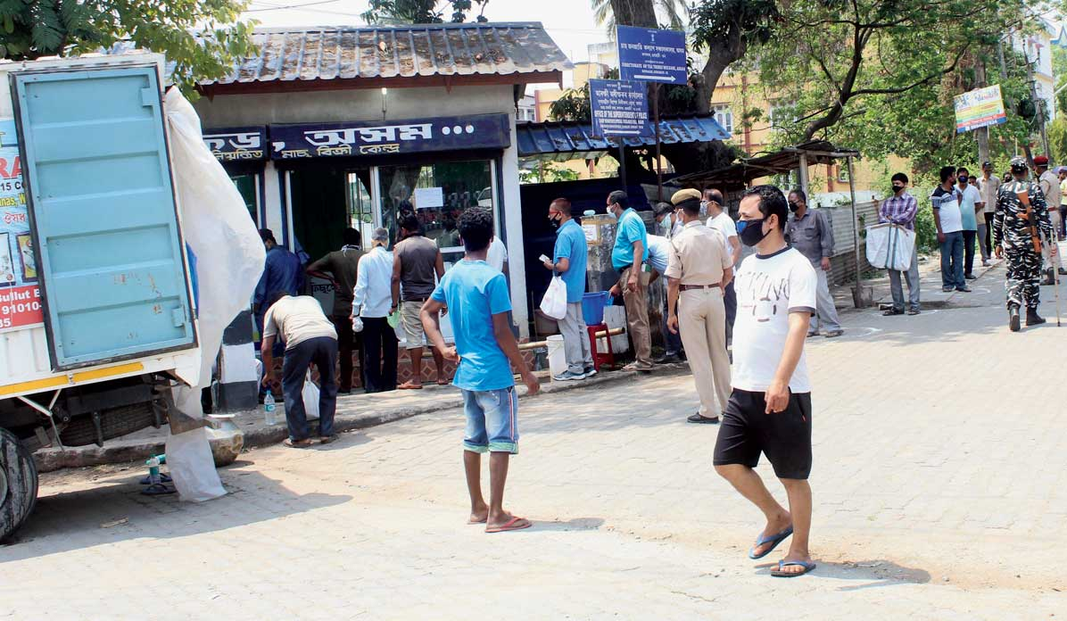 People wait to buy fish from a Fishfed outlet at Rupnagar in Guwahati on Saturday.