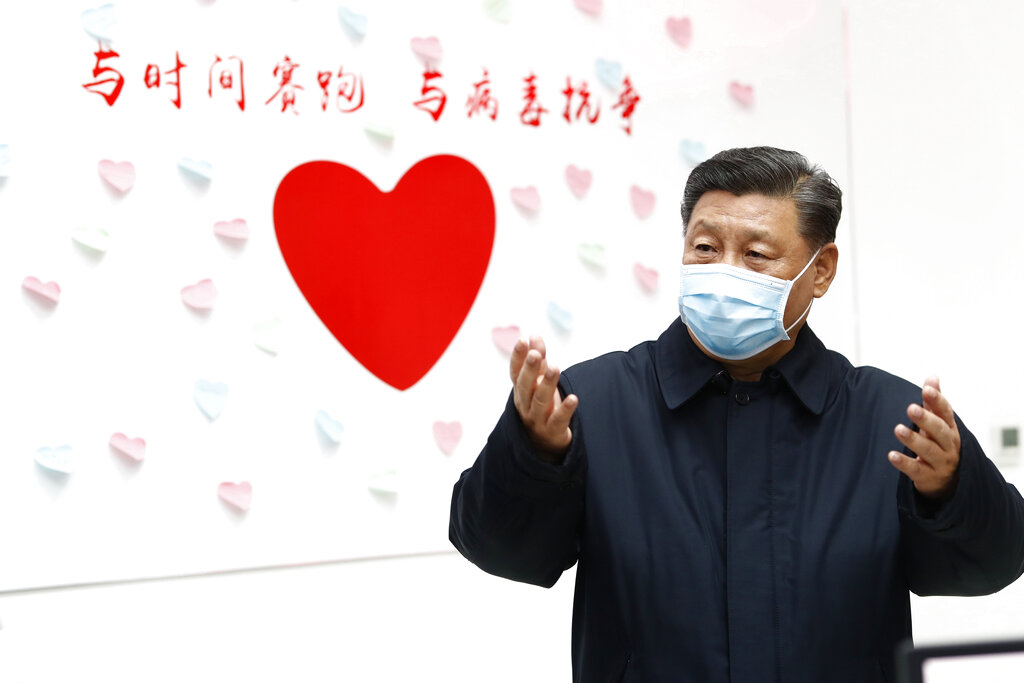 Chinese President Xi Jinping gestures near a heart shape sign and the slogan