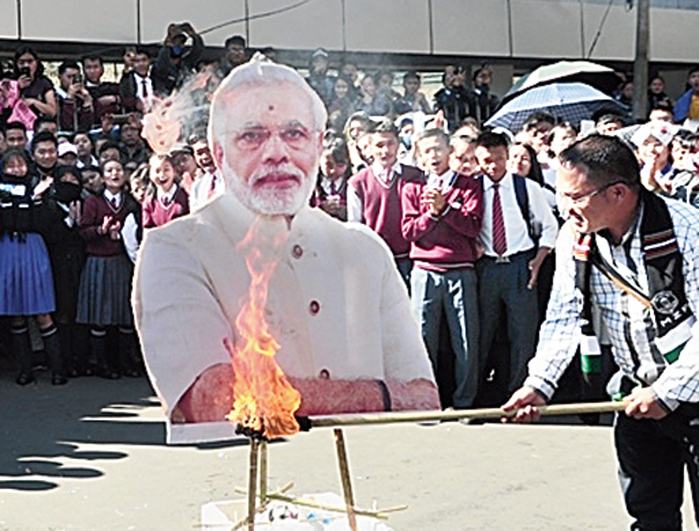 A protester burns an effigy of Narendra Modi in Aizawl on Wednesday.