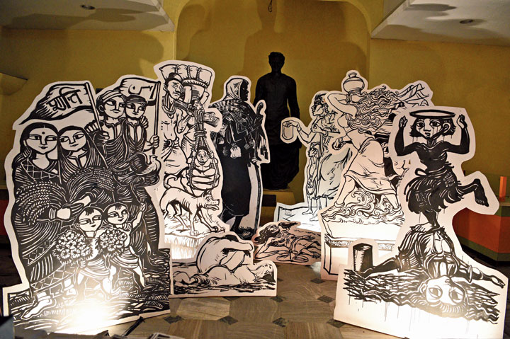 """Some other installations made by Paul. The one in front shows Hindu and Muslim men, women and children with two flags, one with """"peace"""" written in Hindi on it and the other in Urdu. The installation is based on a work of Chittaprosad Bhattacharya. Bhattacharya, who died in penury in 1978, was a member of the undivided Communist party and worked as an artist for the party's publications."""