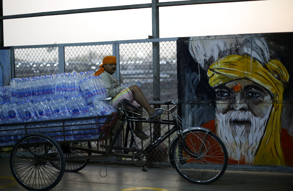 A man sits on a cart loaded with drinking water bottles to distribute to migrant workers arriving on a train from Maharashtra state, in Prayagraj, Saturday, May 30, 2020.