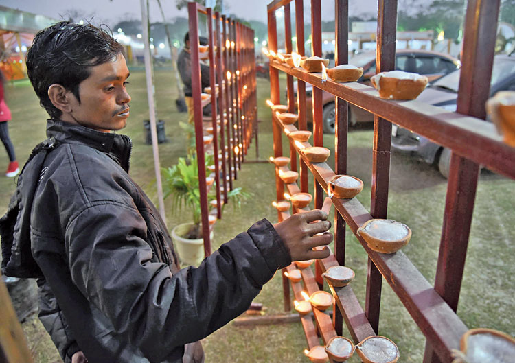 A visitor lights an earthen lamp at the Asam Sahitya Sabha conference at Sualkuchi in Kamrup district on Saturday