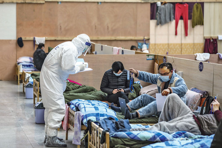 A doctor in a protective suit checks with patients at a temporary hospital in a gymnasium in Wuhan, China