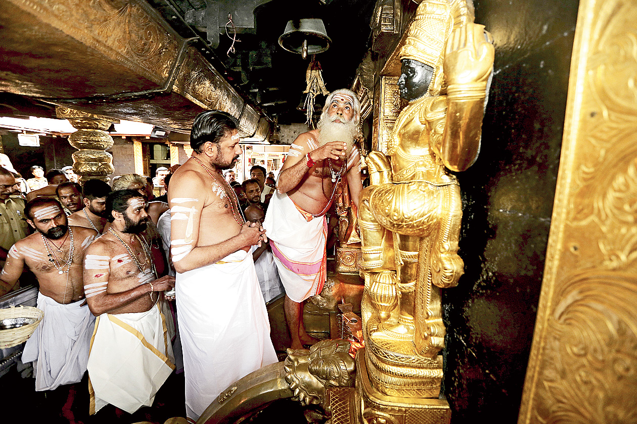 Kandararu Rajeevaru, the tantri or the custodian of the rituals whose presence is required whenever the temple is opened, prays as Unnikrishnan Namboothiri, the melsanti or head priest, prepares to ring the bell as they open the sanctum sanctorum of the Sabarimala temple on Monday