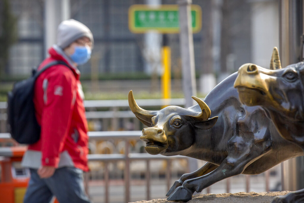 A man wearing a face mask walks past statues of bulls in Beijing, Friday, Feb. 28, 2020. Asian stock markets fell further Friday on spreading virus fears, deepening an global rout after Wall Street endured its biggest one-day drop in nine years.