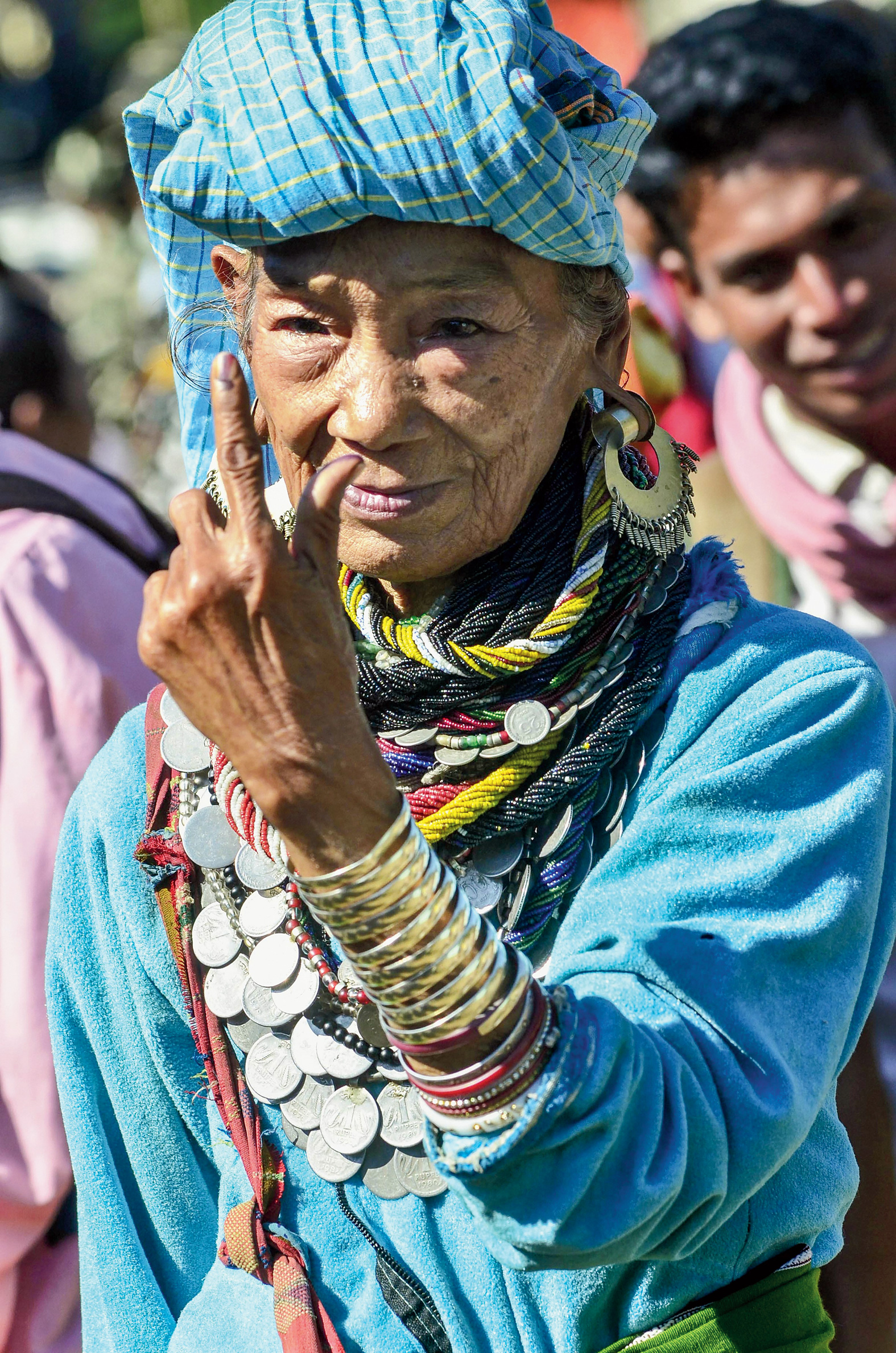 An elderly Bru woman shows her inked finger after casting her vote in Kanhmun on Wednesday.