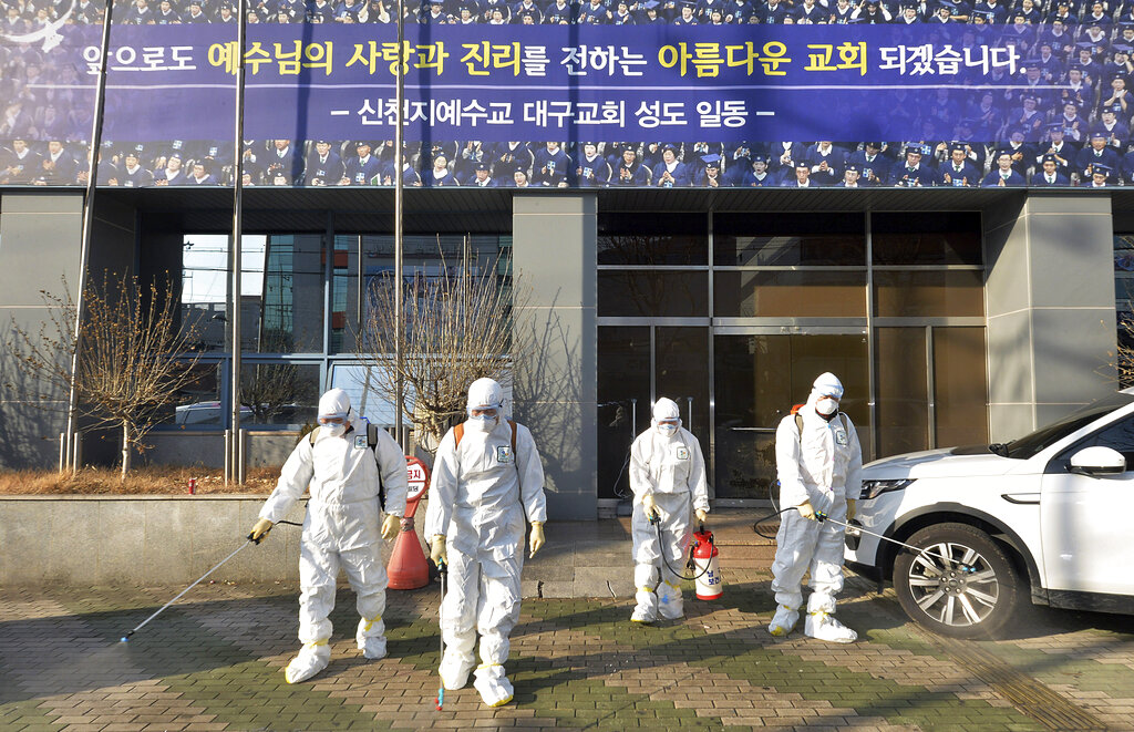 Workers wearing protective gears spray disinfectant against the coronavirus in front of a church in Daegu, South Korea