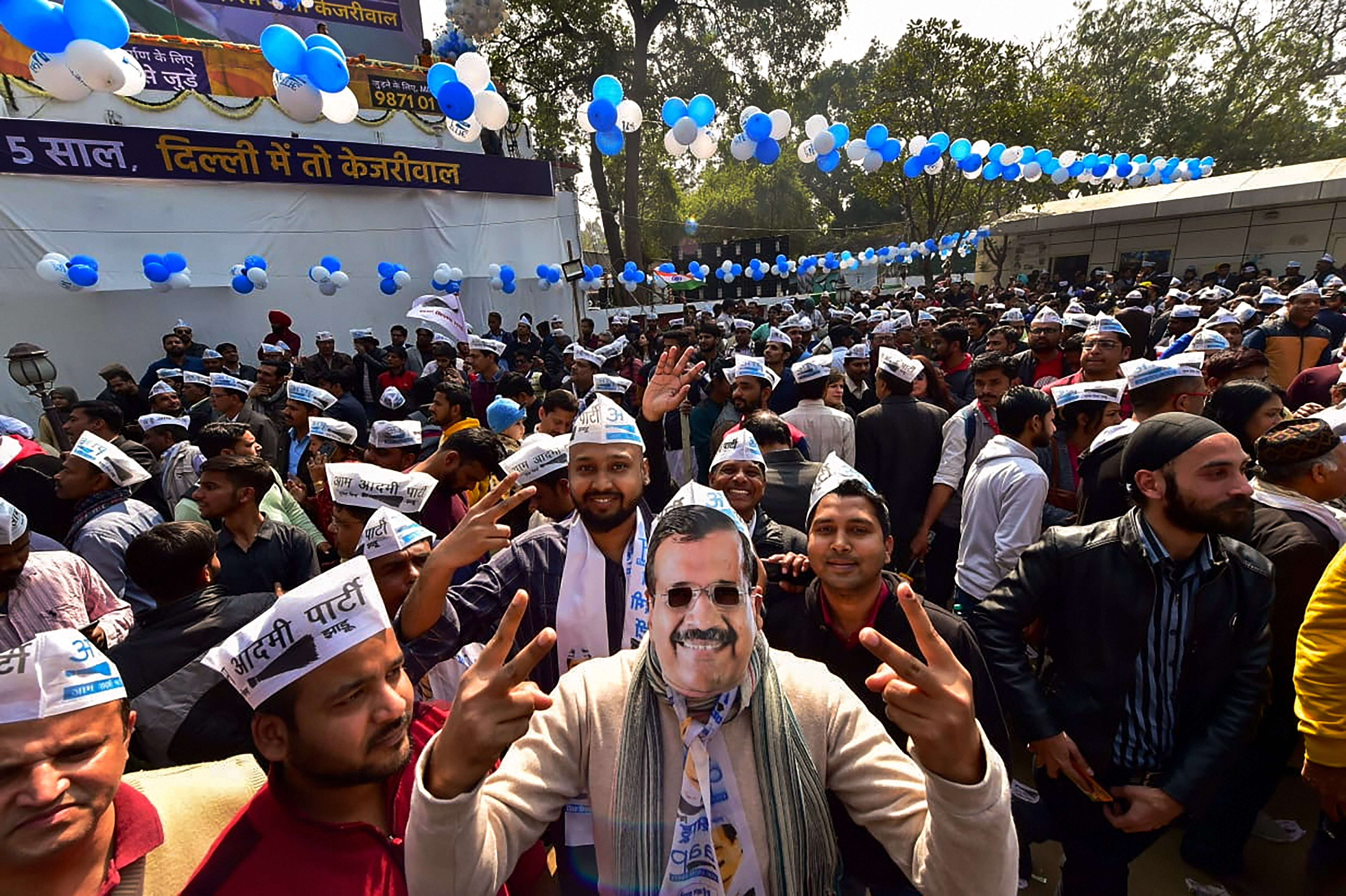An Aam Aadmi Party worker, dressed as party chief Arvind Kejriwal, celebrates along with others the party's success in the Delhi Assembly polls, at party headquarters in New Delhi, Tuesday, February 11, 2020.