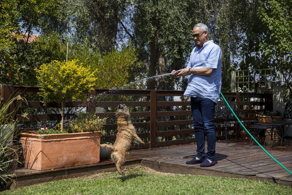 In this Friday, September 13, 2019 photo, Blue and White party leader and former IDF chief of staff Benny Gantz waters his garden and plays with his dog at his home in Rosh Haayin, Israel