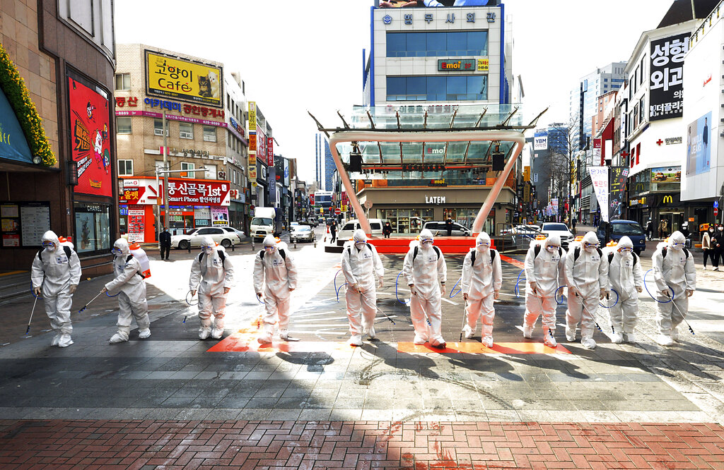 South Korean army soldiers wearing protective suits spray disinfectant to prevent the spread of the COVID-19 virus on a street in Daegu, South Korea