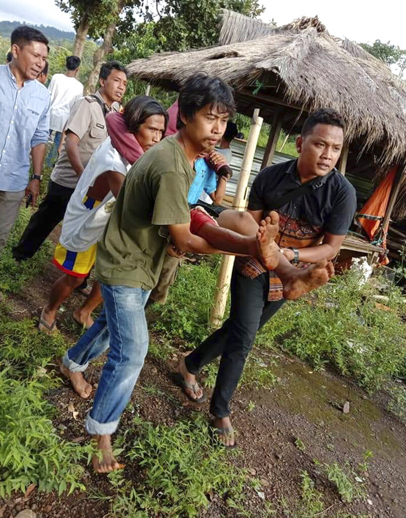 People carry an injured earthquake survivor in Bayan, North Lombok, Indonesia.
