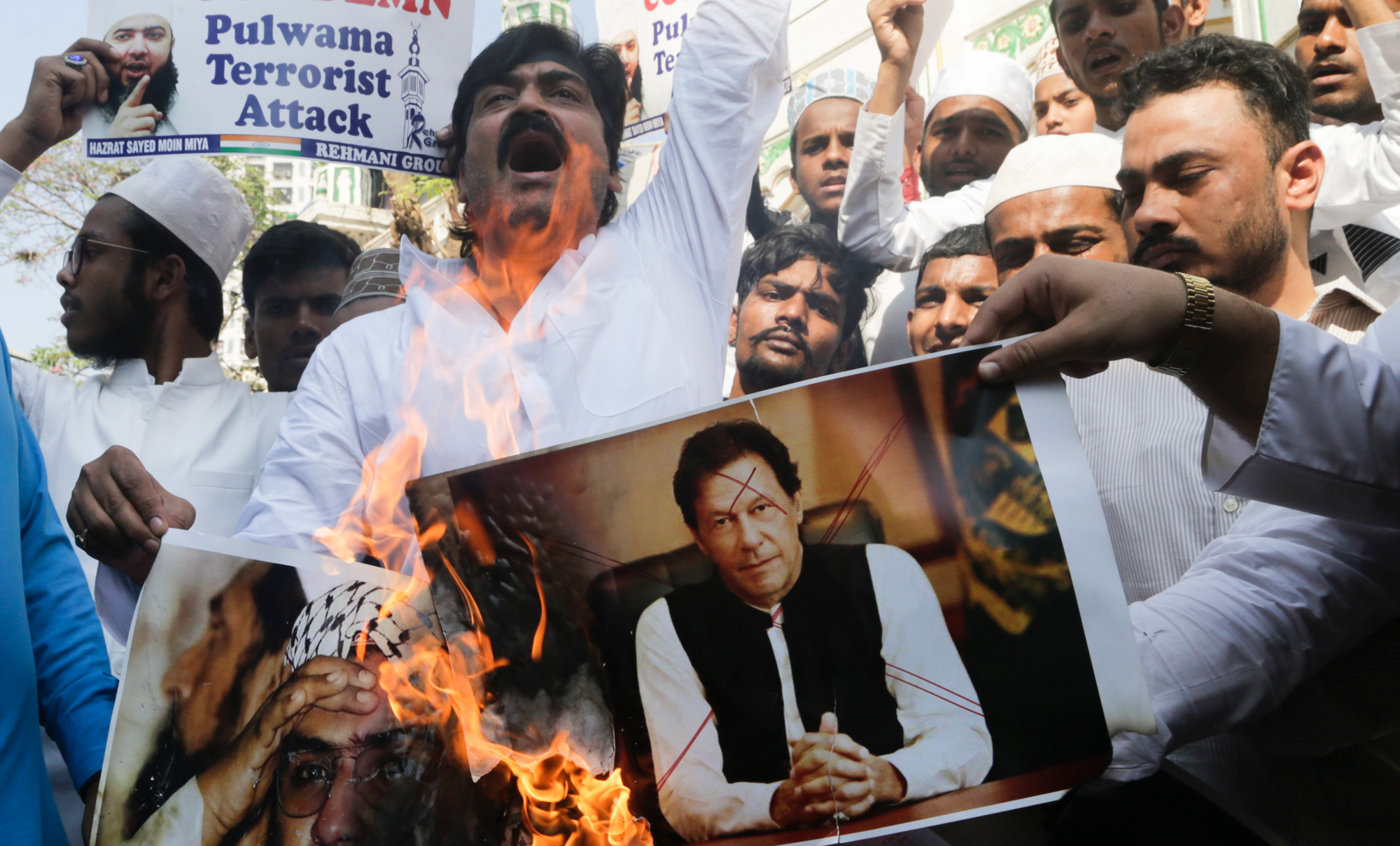 In this Friday, February 15, 2019 file photo, Indian muslims burn posters of Pakistani prime minister Imran Khan (center) and Jaish-e-Mohammed leader Masood Azhar, during a protest against Thursday's attack on a paramilitary convoy in Kashmir, in Mumbai, India.