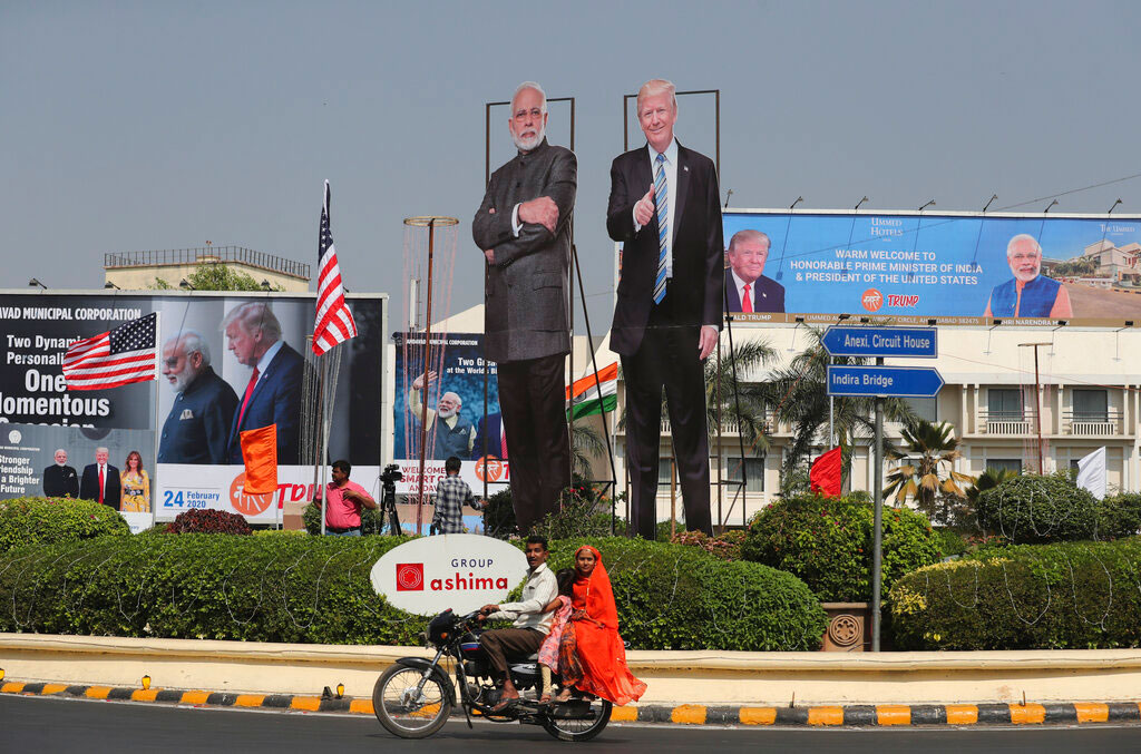 A family rides past huge cut out images of U.S. President Donald Trump and Indian Prime Minister Narendra Modi displayed ahead of Trump's visit in Ahmedabad.