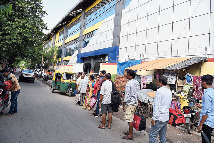 Passengers wait for autos in front of Noapara Metro station