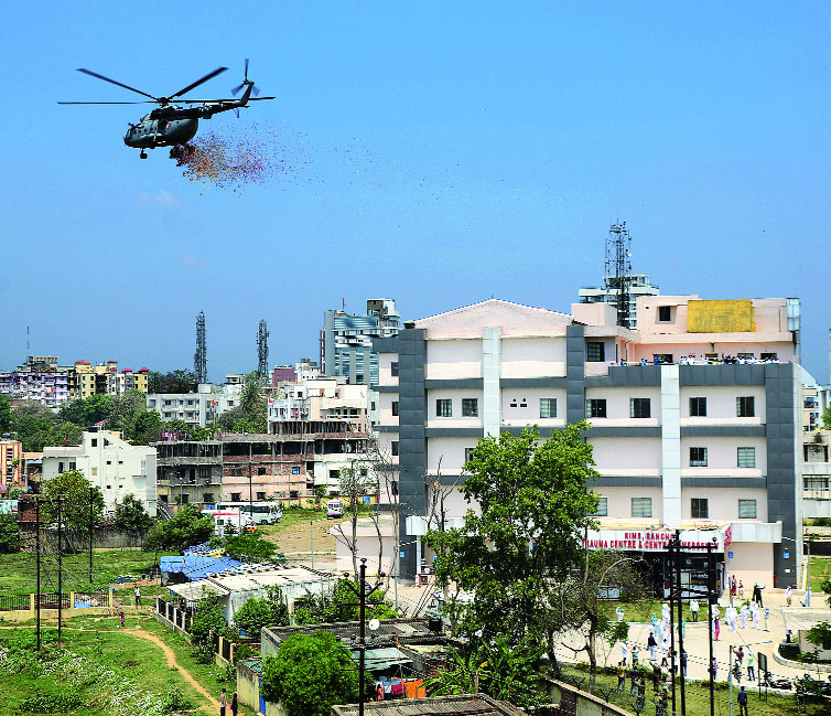 Flower power: A chopper of the Indian Air Force  showers rose petals on the healthcare workers of RIMS in Ranchi on Sunday.