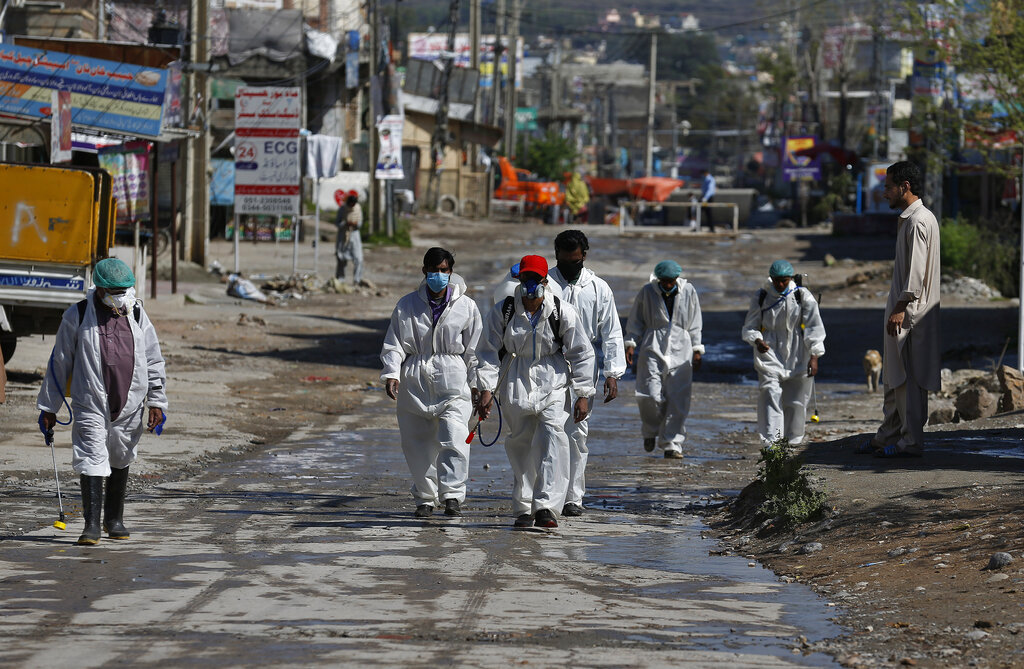 Workers return after a disinfecting an area to try to curb the spread of coronavirus outbreak, in Islamabad, Pakistan, Sunday, March 29, 2020