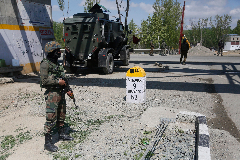 A soldier stands guard on a highway near Srinagar