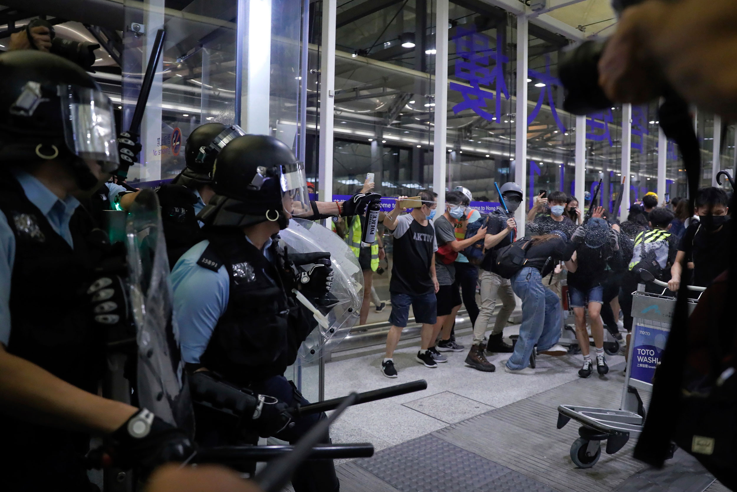 Police officers clash with anti-government protesters at the airport in Hong Kong on Tuesday.