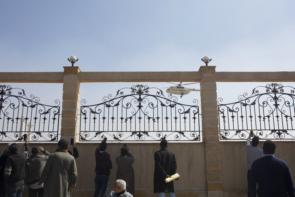 Supporters of ousted President Hosni Mubarak film a helicopter bringing the body of former President Hosni Mubarak, before his funeral in New Cairo, Egypt, Wednesday, Feb. 26, 2020. Egypt is holding a full-honors military funeral for Mubarak who was ousted from power in the 2011 Arab Spring uprising. Mubarak, 91, died Tuesday at a Cairo military hospital from heart and kidney complications.