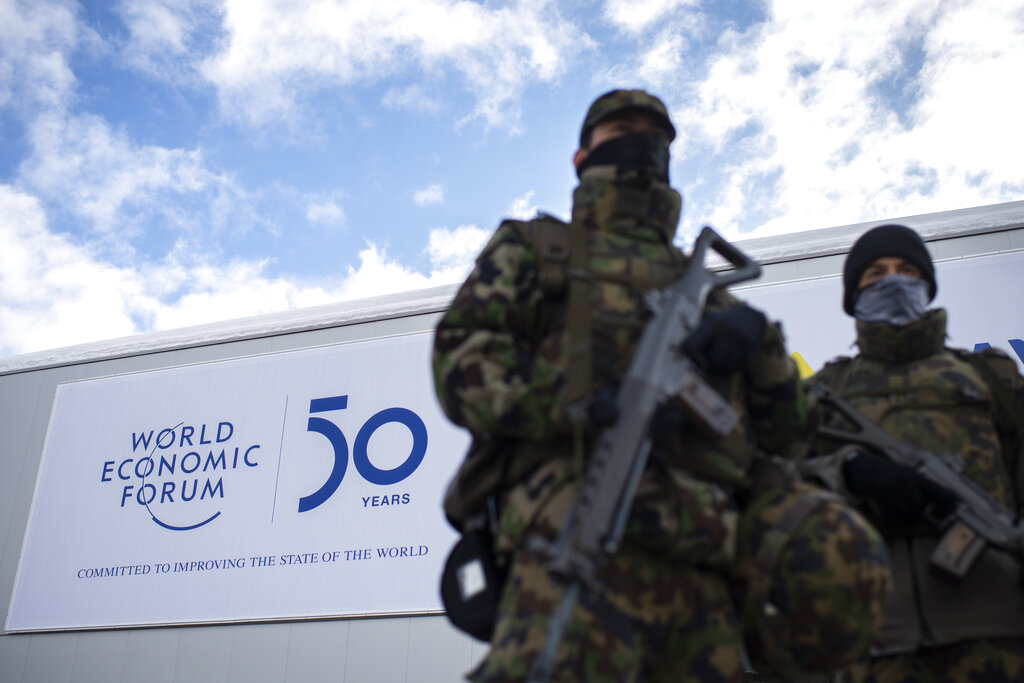 The logo of the WEF is seen behind soldiers of the Swiss Army on guard outside the congress center prior the 50th annual meeting of the World Economic Forum, WEF, in Davos, Switzerland, Sunday, Janjuary 19, 2020