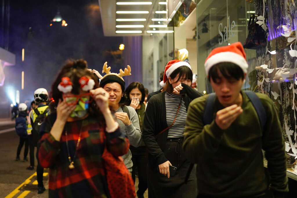 Residents dressed for Christmas react to tear gas as police confront protesters on Christmas Eve in Hong Kong on Tuesday.