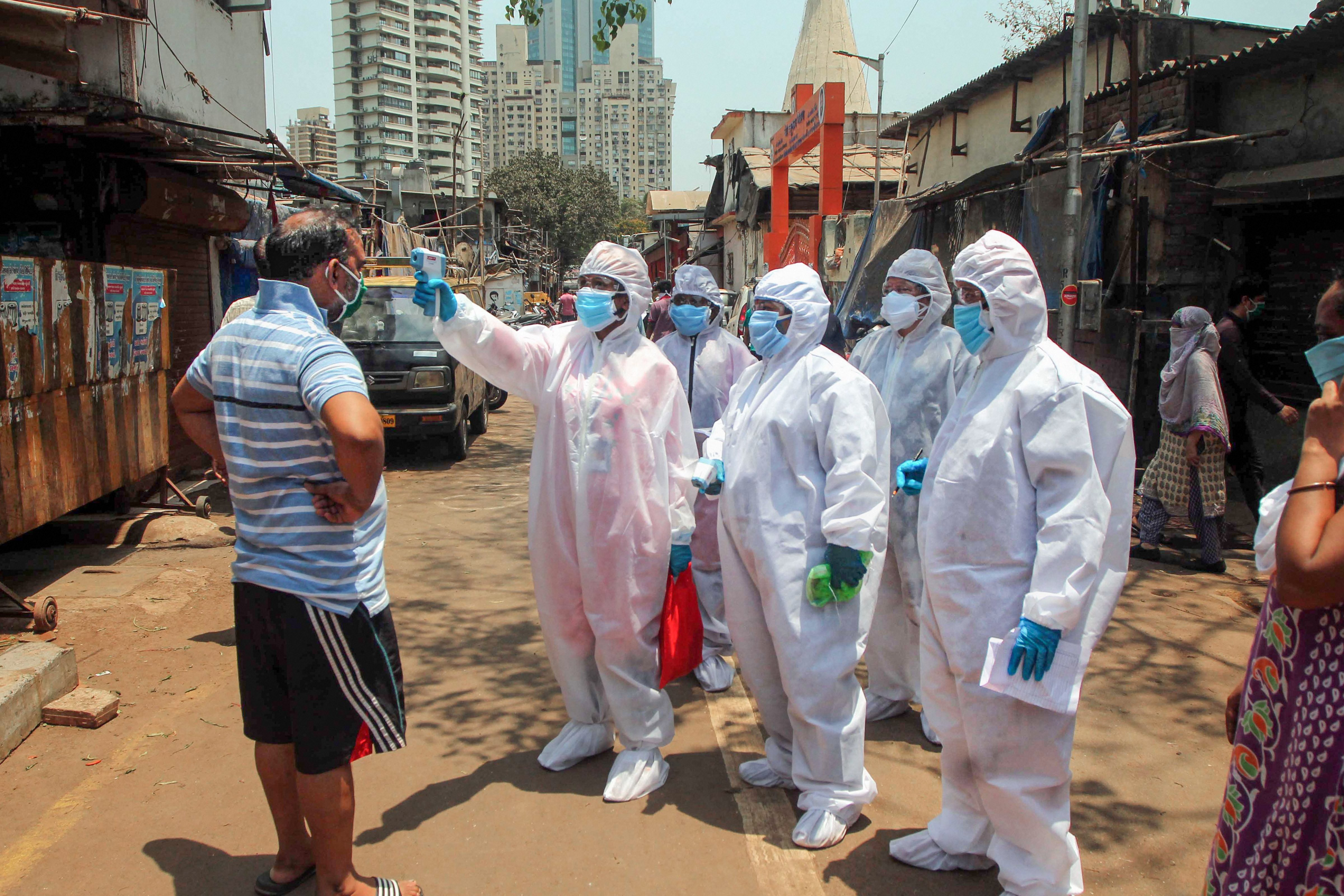 Doctors wearing protective suits check residents with an electronic thermometer inside a slum in Worli during the nationwide lockdown to curb the spread of coronavirus in Mumbai, Friday, April 17, 2020.