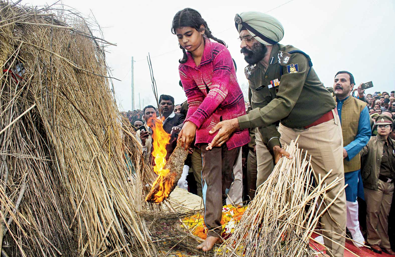 Supriya, 12, lights the funeral pyre of her father Pradeep Singh Yadav in Kannauj, Uttar Pradesh. She fainted while she was lighting it.