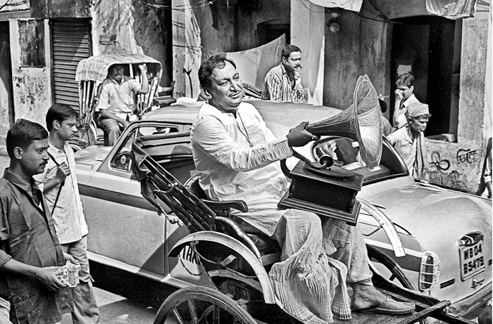"""Central Calcutta. A man in a rickshaw with a gramophone. One might presume the photograph is  of an old Calcutta, taken some time 70 to 80 years ago. But there are giveaways aplenty that will help the viewer date the picture correctly. """"There is a conflict of time and space,"""" says Saha enigmatically."""