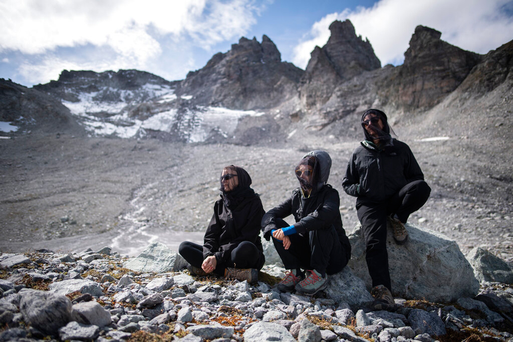 Activists in dark clothing wearing mourning veils during a commemoration near the 'dying' glacier of Pizol mountain in Wangs, Switzerland, on Sunday