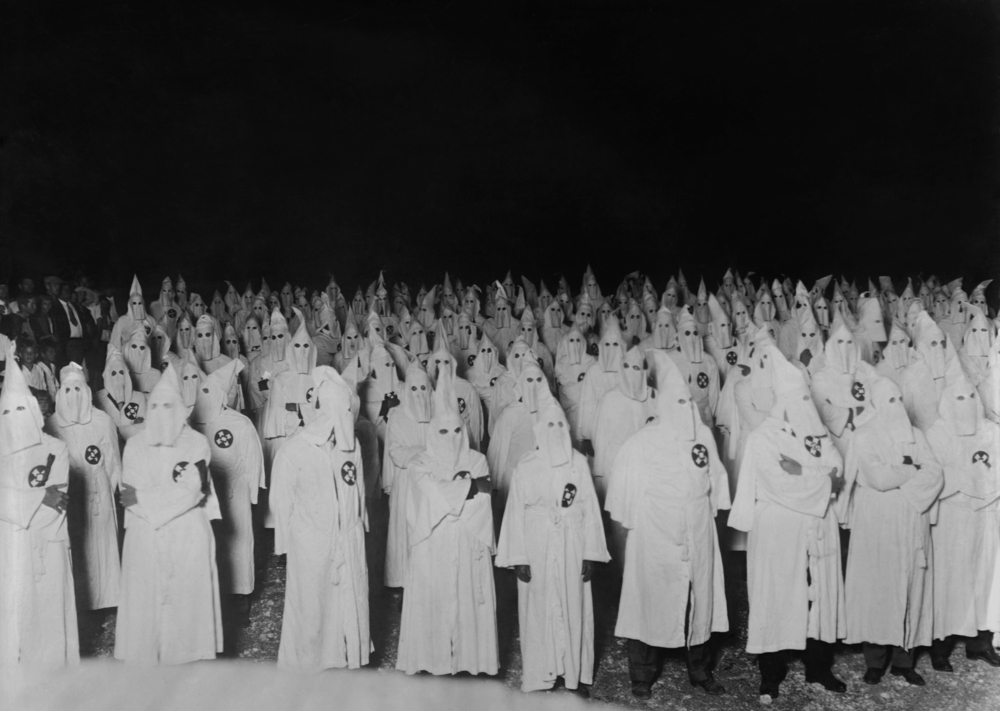 Members of the American white supremacist organization, Ku Klux Klan, dressed in ceremonial robes and hoods